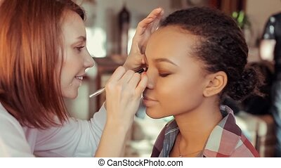 Makeup artist paints eyelashes a young African model.