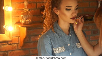 makeup artist paints her lips a young beautiful girl