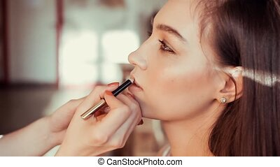Makeup artist paints lips beautiful young model.