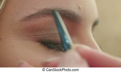 Makeup artist paints the eyebrows, doing eyebrow correction....