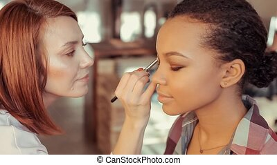 Makeup artist paints the eyelid of a young African model.