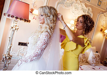 makeup artist preparing bride before the wedding in a...