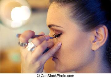 Makeup artist put artificial eyelashes on model
