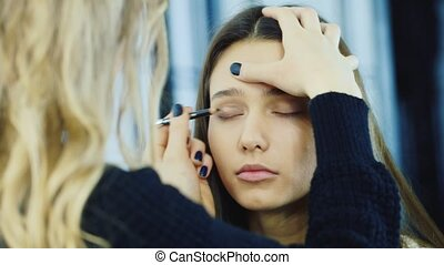 Makeup artist puts eye makeup on young woman