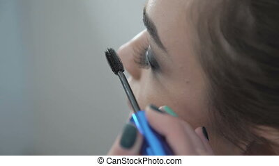 Makeup artist putting on mascara
