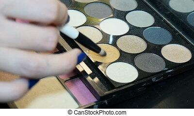 Makeup artist uses a beautiful eye shadow.