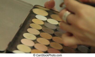 Makeup artist uses a brush and palette eye shadow