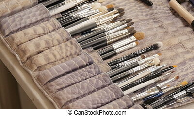 Makeup artist uses a variety of brush for the job.