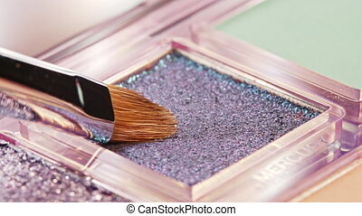 Makeup artist working with eyeshadows palette. Brush gains pigment on pile to be used in make-up. Macro view of working process, tools in beauty industry. Concept of decorative cosmetics, visagist.