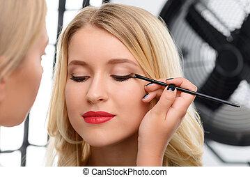 Eye makeup. Female makeup artist is busy applying professional eye shadows.