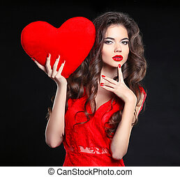 Makeup. Beautiful brunette girl in red with heart gift for Valentines Day. Manicured nails.  Beauty portrait of young woman with chaplet isolated on black background.