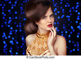Makeup. Beautiful fashion woman in gold, elegant lady in expensive pendant jewelry close-up. Beauty Hairstyle. Attractive brunette over blue party lights background.
