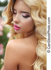 Makeup. Beautiful girl with blond long wavy hair. Fashion model in park.