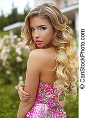 Makeup. Beautiful girl with blond long wavy hair posing in Fashion dress, attractive model in blossom park.
