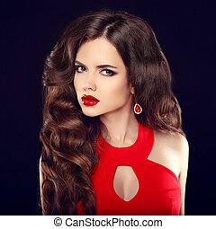 Makeup. Beautiful girl with long wavy hair in red dress isolated on black studio background. Fashion earring jewelry.