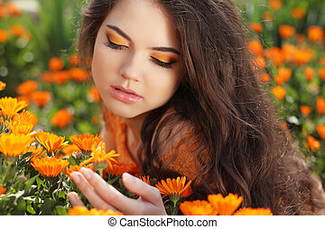 Makeup. Beauty Long Wavy Hair. Beautiful Brunette Woman over marigold flowers. Healthy Hairstyle. Outdoors portrait.