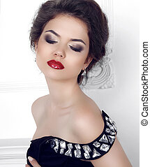 Makeup. Beauty portrait of brunette sexy girl model posing in fashion dress