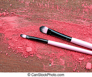 Makeup brush and crushed eyeshadows on wooden background
