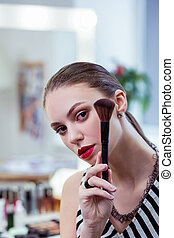 Nice young woman standing with a powder brush - Makeup brush...