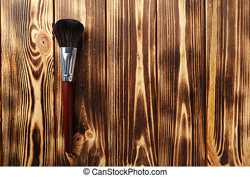 Makeup brush on a brown wooden background