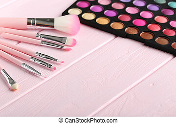 Makeup brush set with palette on a pink wooden table