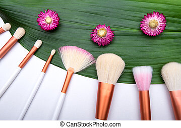 Makeup Brushes on green leaf with small flowers