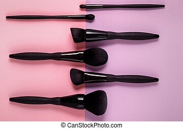 makeup brushes on pastel paper pink background