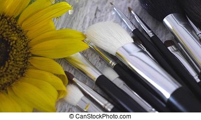 Makeup brushes on table next to flowers