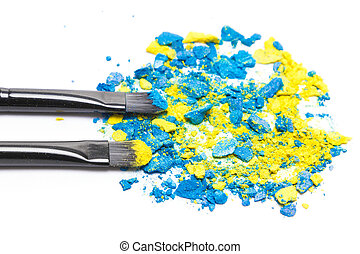 Makeup brushes with crushed compact blue and yellow...