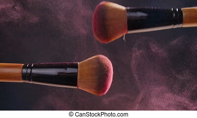 Makeup brushes with powder on dark background