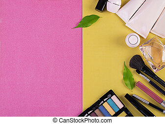 Makeup cosmetics on pink-yellow background. Top view. Copy space