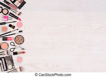 Makeup cosmetics on whiie wooden background