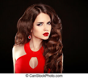 Makeup. Elegant woman. Fashion earring jewelry. Beautiful girl with long wavy hair in red dress isolated on black studio background.