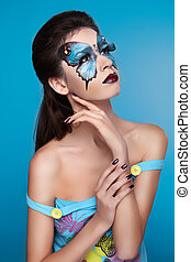 Makeup. Fashion face art portrait. Beautiful model girl posing isolated on blue background.