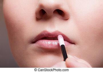 Makeup. Girl applying lipgloss lipstick on lips. Part of face.
