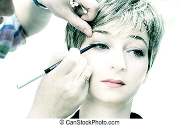 Makeup - High key image of a makeup artist applying a...