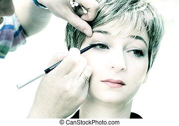 Makeup - High key image of a makeup artist applying a...