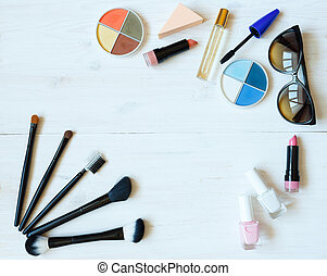 Makeup products on white wooden background with copyspace
