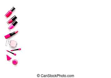 Makeup set. Eyeshadows, lipstick, nailpolish, applicators on white background top view copyspace
