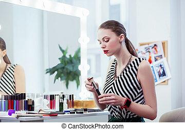 Beautiful young woman holding a makeup brush