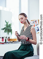 Delighted nice woman looking at the brush - Makeup tools. ...