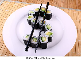 Maki Sushi as dollar sign on white plate, closeup
