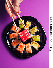 Maki sushi on purple background with gift box in hand