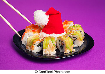 Maki sushi on purple background with santa hat