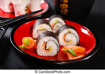 maki sushi on red plate and sake - japanese maki sushi rolls...