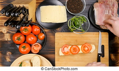 Making a delicious healthy sandwich at the kitchen on wooden board