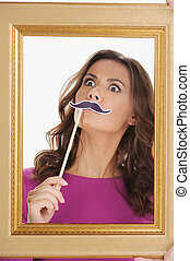 Making a face. Beautiful young women looking through picture frame and holding a face moustache in front of her face while isolated on white