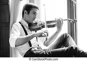 Making a magic sound. Handsome young man sitting on the...