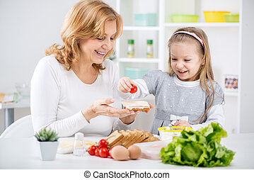 Making a Sandwich - Beautiful happy grandmother and her cute...