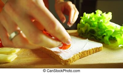 Making a sandwich: putting cherry tomatoes on bread